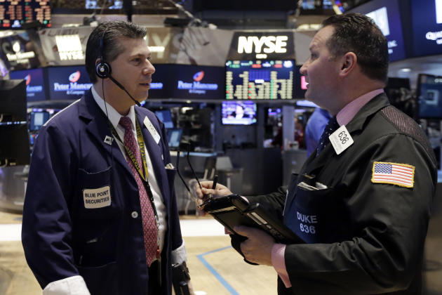 Traders William McInerney, left, and Edward Curran confer on the floor of the New York Stock Exchange, Friday, March 6, 2015. Stocks opened lower on Friday as another strong U.S. jobs report raised th
