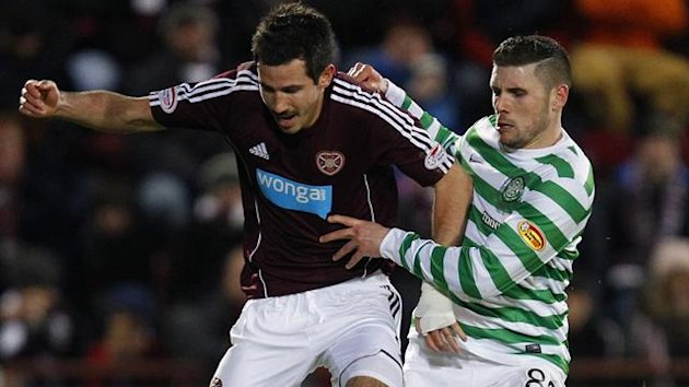 Hearts' Ryan McGowan (L) runs with the ball as Celtic's Gary Hooper challenges (Reuters)