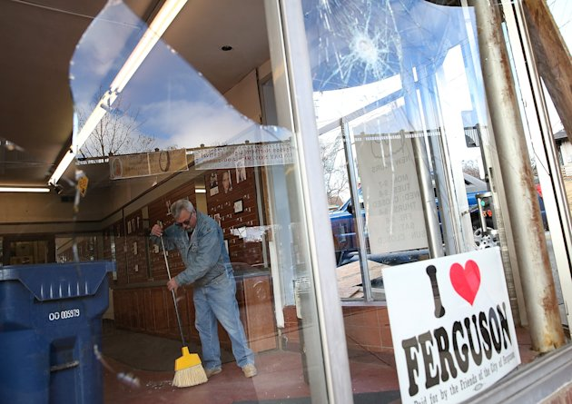 A worker cleans up glass at a business that was damaged during a demonstration in Ferguson (Getty)
