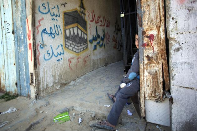 A Palestinian boy sits next to an old wall mural depicting the Kaaba, Islam's holiest site and a center point of the annual Hajj pilgrimage, in the Rafah refugee camp, southern Gaza Strip, Friday,