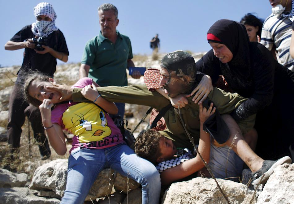 Palestinians scuffle with an Israeli soldier as they try to prevent him from detaining a boy during a protest against Jewish settlements in the West Bank village of Nabi Saleh near Ramallah