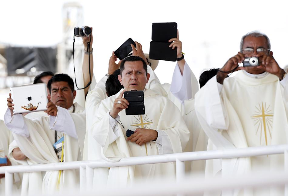 Priests take pictures as Pope Francis arrives to lead a mass at the Los Samanes park in Guayaquil