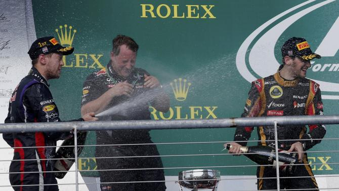 Sebastian Vettel of Germany and Romain Grosjean of France spray champagne next to Matt Cadieux during celebrations on the podium after the Austin F1 Grand Prix at the Circuit of the Americas in Austin