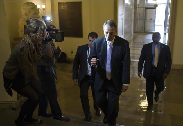Boehner playfully pumps his fist in response to a reporter's question as he arrives at the U.S. Capitol in Washington