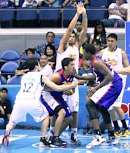 Air21's Nonoy Baclao is double-teamed by TNT's Rabeh Al-Hussaini and Larry Fonacier. (PBA Images)