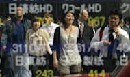This file photo shows pedestrians reflected on a share prices board in Tokyo, in 2011. Japan's unemployment rate improved slightly to 4.3 percent in June from 4.4 percent in May, the internal affairs ministry said on Tuesday