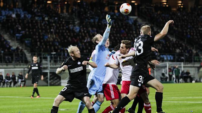 RB Salzburg's goalkeeper Peter Gulacsi, second left, clears the ball between Esbjerg fB's Hans Henrik Andreasen, left, and Jens Berthel Askou, right, during the Europa League group C soccer match, Thursday, Oct. 3, 2013 in Esbjerg, Denmark