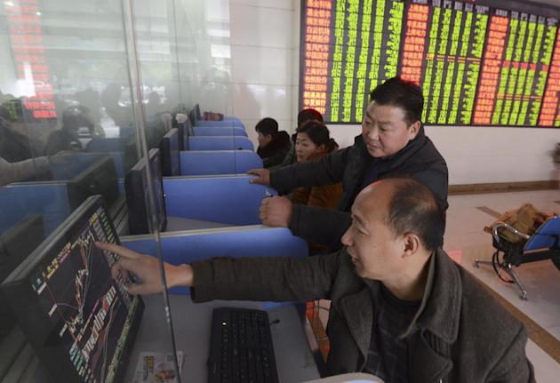 Chinese investors check stock prices on computer terminals at a brokerage house in Fuyang in central China's Anhui province Friday, Nov. 27, 2015. China's stock market fell sharply Friday as i