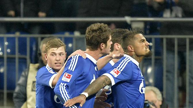 Schalke's Kevin-Prince Boateng of Ghana, right, leads his team after scoring the decisive goal during the German Bundesliga soccer match between FC Schalke 04 and VfL Wolfsburg in Gelsenkirchen,  Germany, Saturday, Feb. 1, 2014
