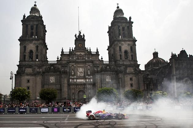 A Redbull driver rolls past the Metropolitan Cathedral during a Formula One exhibition in Mexico City's main plaza, the Zocalo, Saturday, June 27, 2015. Mexico last held an F1 race in 1992 at Auto