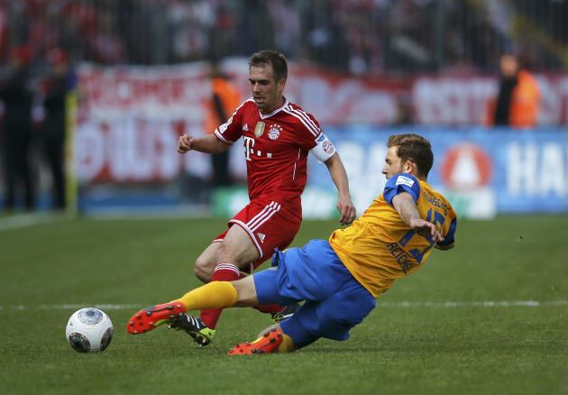 Bayern Munich's Lahm is tackled by Eintracht Braunschweig's Reichel during their Bundesliga soccer match in Berlin