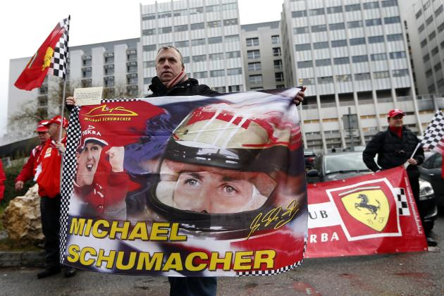 Philippe, a fan from Lyon, waves a flag as he attends a silent 45th birthday tribute to seven-times former Formula One world champion Michael Schumacher in front of the CHU hospital emergency unit in