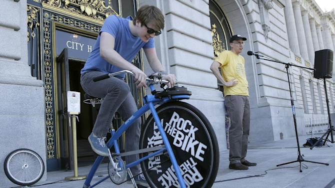 """Bill McKibben, founder of 350.org, right, speaks to a crowd of college students and supporters at a rally to support fossil fuel divestment outside of City Hall in San Francisco, Thursday, May 2, 2013. Hayden Higgins, left, rides a Rock The Bike """"One Bike/One Speaker,"""" a bicycle that generated power for the sound system at the rally. (AP Photo/Jeff Chiu)"""