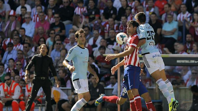 Atletico de Madrid's Diego Costa from Brazil, second right, in action with Celta de Vigo's David Costas, right, and Borja Oubina, second left,  during a Spanish La Liga soccer match at the Vicente Calderon stadium in Madrid, Spain, Sunday, Oct. 6, 2013