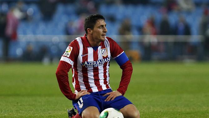 Atletico's Cristian Rodriguez from Uruguay kneels during a Copa del Rey soccer match between Atletico de Madrid and Sant Andreu at the Vicente Calderon stadium in Madrid, Spain, Wednesday, Dec. 18, 2013