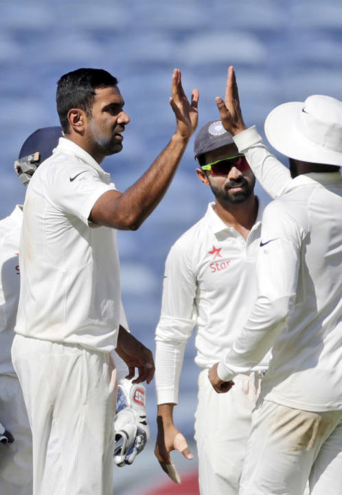 India's Ravichandran Ashwin, left celebrates with teammates the dismissal of Australia's Matt Renshaw's  during the first day of the first test cricket match in Pune, India, Thursday, Feb.