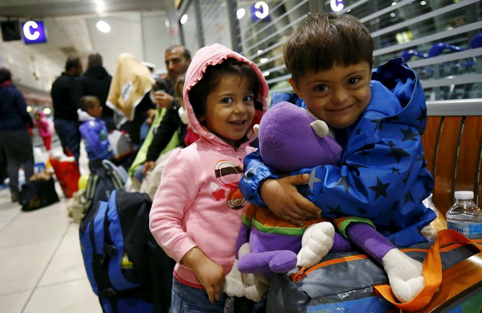 Two Syrian children laugh as they cuddle a stuffed toy given by wellwishers after they arrived with a train from Budapest's Keleti station at the railway station of the airport in Frankfurt