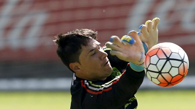 Mexico's goalkeeper Moises Munoz dives for a ball during a soccer training session in Mexico City