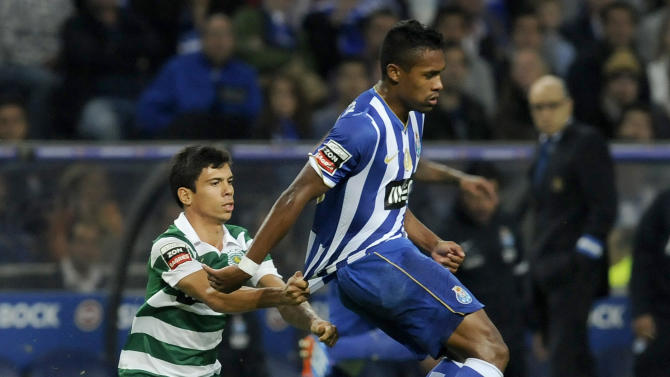 Sporting's Andre Martins, left, grabs FC Porto's Danilo Silva, from Brazil, during a Portuguese League soccer match at the Dragao stadium in Porto, Portugal, Sunday, Oct. 27, 2013. Danilo scored once in Porto's 3-1 victory