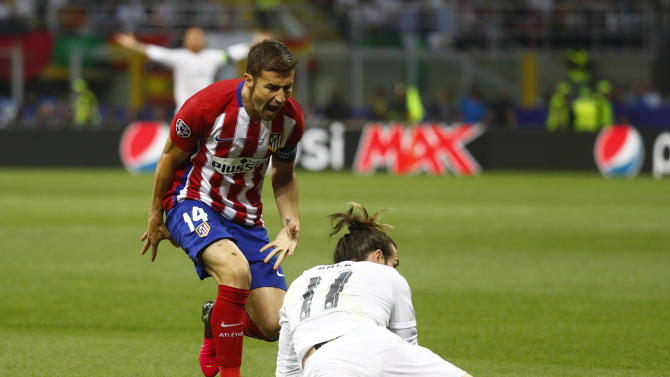 Atletico Madrid's Gabi reacts as Real Madrid's Gareth Baleis on the floor