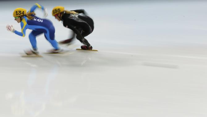 Inna Simonova of Kazakhstan and Emily Scott of the US participate in the women's 1,000 metres short track heat event at the Iceberg Skating Palace during the Sochi 2014 Winter Olympics