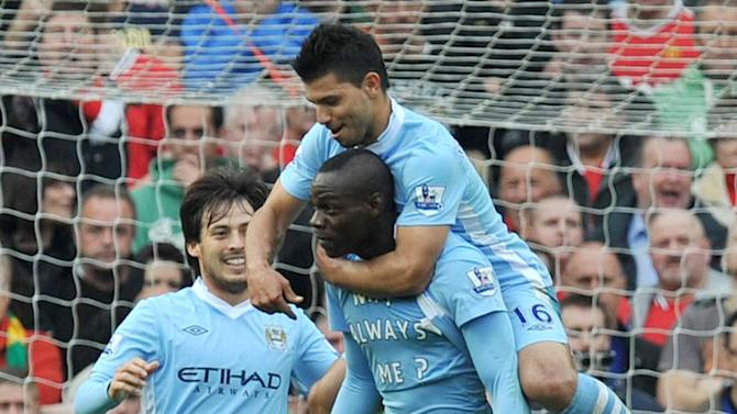 Manchester City's Sergio Aguero jumps on the back of goalscorer Mario Balotelli during the English  Premier League match  against Manchester United at Old Trafford, Manchester England  Sunday Oct. 23, 2011.  (AP Photo/Martin Rickett/PA)  UNITED KINGDOM OUT