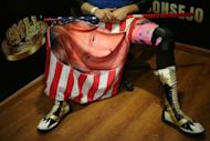 U.S. wrestler Sam Adonis, 27, role-playing as a fan of U.S. President Donald Trump, holds a flag with Trump's face in a interview before a wrestling fight at the Coliseo Arena, in Mexico City, Mexico, February 12, 2017. REUTERS/Edgard Garrido