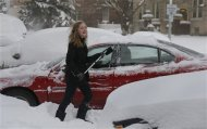 Grace Rogers cleans the snow off her car in the midtown neighborhood of Detroit, Michigan January 6, 2014. REUTERS/Rebecca Cook