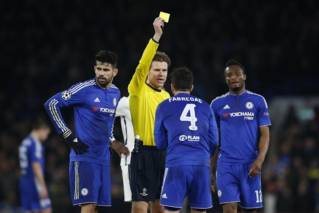 Referee Felix Brych shows a yellow card to Chelsea's Cesc Fabregas