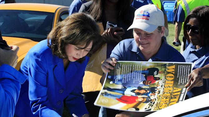U.S. Secretary of Labor Hilda Solis signs autographs outside the Flat Rock Assembly in Flat Rock, Mich., Monday, Sept. 10, 2012. The plant, formerly known as AutoAlliance International will continue to produce the Mustang and add the Fusion next year. Flat Rock Assembly will be the U.S. producer of the Fusion, employing 2,900 workers on both vehicle lines. (AP Photo/Carlos Osorio)