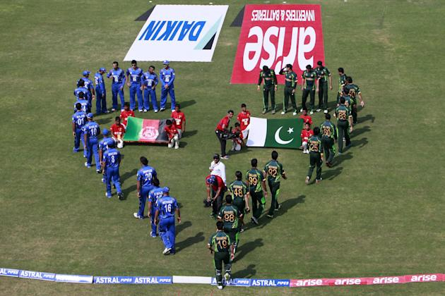Afghanistan players, left in blue, and Pakistan players, right, walk on the cricket field before their match in the Asia Cup one-day international cricket tournament in Fatullah, near Dhaka, Banglades