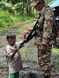 A young boy is seen touching the rifle of a Moro Islamic Liberation Front (MILF) rebel inside the group's base at Camp Darapan, Sultan Kudarat province, on the southern Philippine island of Mindanao, in 2011. MILF rebels waging a decades-long insurgency in which more than 150,000 people have died are aiming to sign a roadmap for peace this year, according to their chief negotiator