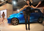 Models perform in front of Toyota's Etios concept car during an auto expo in New Delhi, in 2010. Toyota said on Friday it would roll out a number of new compact cars priced around $12,500 in developing nations, targeting sales of more than one million of the models annually in emerging markets by 2015