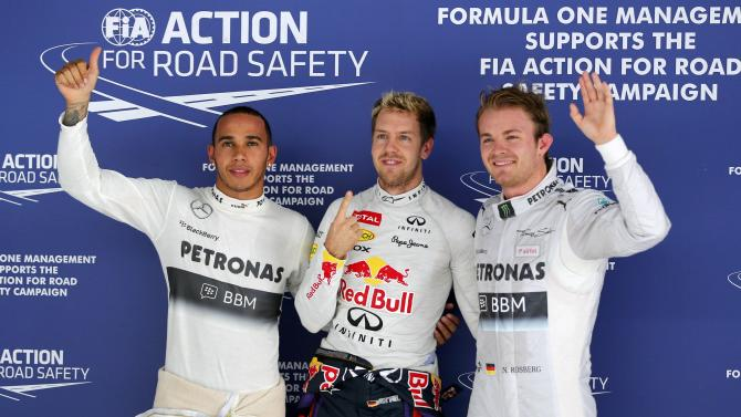Mercedes Formula One driver Hamilton, Red Bull Formula One driver Vettel and Mercedes Formula One driver Rosberg pose after the qualifying session of the Indian F1 Grand Prix at the Buddh International Circuit in Greater Noida