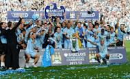 Manchester City players celebrate with the Premier League trophy after their 3-2 victory over Queens Park Rangers in the English Premier League football match between Manchester City and Queens Park Rangers at The Etihad stadium in Manchester
