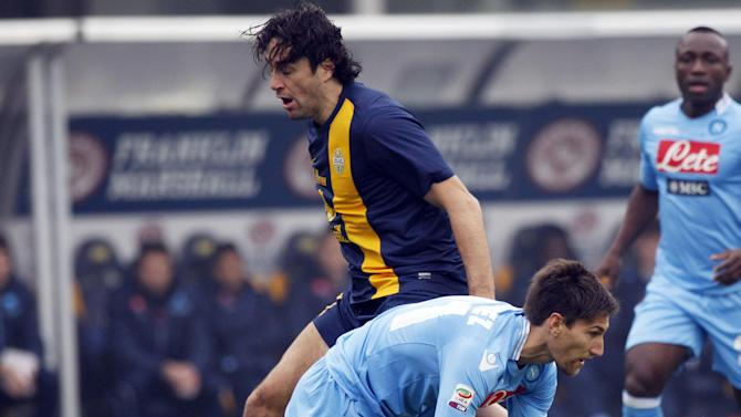 Napoli's Federico Fernandez, bottom, of Argentina, and Hellas Verona's Luca Toni challenge for a ball during a Serie A soccer match at the Bentegodi stadium in Verona, Italy, Sunday, Jan. 12, 2014
