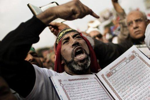 "A supporter of Egypt's President Mohamed Morsi and the Muslim Brotherhood holds a copy of the Koran in Cairo's Nasr City on December 14, 2012. The opposition accused President Mohamed Morsi's Muslim Brotherhood of attempted ""vote rigging"" in Saturday's referendum on a new constitution for Egypt."