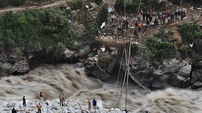 Water gushes down a river as Indian paramilitary soldiers stand near a temporary bridge after it was damaged as stranded pilgrims wait to be evacuated on the other side in Govindghat, India, Saturday, June 22, 2013. Soldiers were working to evacuate tens of thousands of people still stranded Saturday in northern India where nearly 600 people have been killed in monsoon flooding and landslides. (AP Photo/Rafiq Maqbool)
