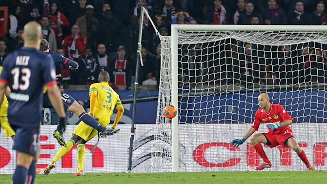 Paris Saint Germain's Zlatan Ibrahimovic of Sweden, partly seen at left, scores the fifth goal for Paris, as Nantes goalkeeper Remy Riou prepares to jump, during the League One soccer match between Paris Saint Germain and Nantes at the Parc des Princes stadium in Paris, Sunday Jan. 19, 2014