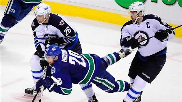 Vancouver Canucks forward Chris Higgins (20) is checked by Winnipeg Jets forward Andrew Ladd (16) and forward Blake Wheeler (26) during the third period at Rogers Arena (Reuters)