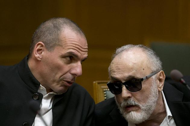 Greek Finance Minister Yanis Varoufakis, left, chats with Health Minister Panagiotis Kouroublis at a Cabinet Meeting in Athens, on Sunday, March 29, 2015. Greece is going through difficult talks with