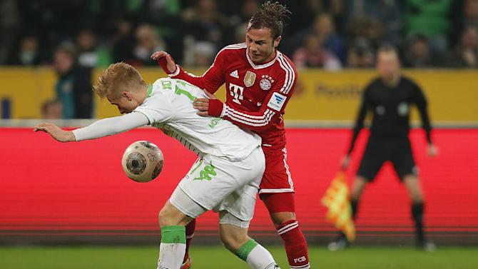 Moenchengladbach's Oscar Wendt of Sweden, left, and Bayern's Mario Goetze challenge for the ball during the German first division Bundesliga soccer match between VfL Borussia Moenchengladbach and Bayern Munich in Moenchengladbach, Germany, Friday, Jan. 24, 2014