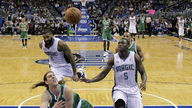 Boston Celtics' Kelly Olynyk takes a shot after he was tripped up by Orlando Magic's Kyle O'Quinn (2) on his way to the basket as Victor Oladipo (5) runs along side of him during the second half of an NBA basketball game in Orlando, Fla., Sunday, Jan. 19, 2014. Orlando won 93-91