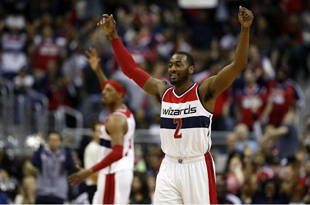 Washington Wizards guard John Wall (2) celebrates with forward Paul Pierce, behind, in the second half of Game 4 in the first round of the NBA basketball playoffs against the Toronto Raptors, Sunday,