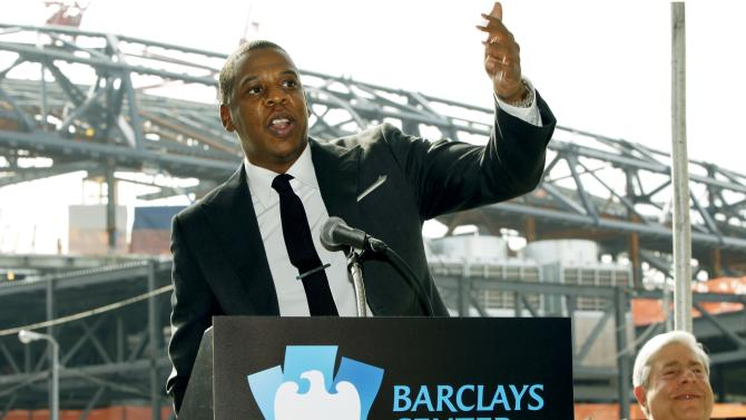 "FILE - In this Sept. 26, 2011 file photo, entertainer Shawn ""Jay-Z"" Carter gestures during a news conference in front of Barclays Center, under construction in the background, as Brooklyn borough President Marty Markowitz, right, applauds in downtown Brooklyn, N.Y. Jay-Z, who is also the co-owner of the Brooklyn Nets, will open the team's new 18,000-seat arena with a concert series beginning on Friday, Sept. 28, 2012. (AP Photo/Kathy Willens, File)"