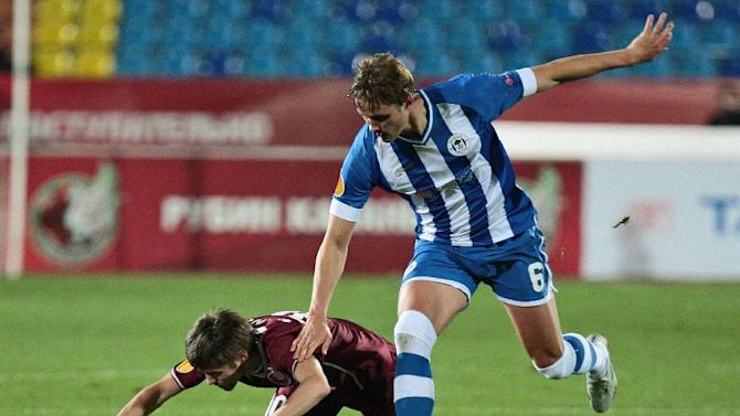 Rubin Kazan's Dmitri Torbinski, left, falls down as he fights for a ball with Wigan Athletic's Thomas Rogne during their Europa League group D soccer match  in Kazan, Russia, Thursday Nov. 7, 2013