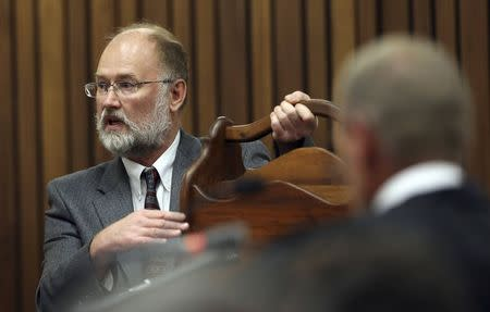 Defense expert witness Dixon holds a magazine rack as Prosecutor Nel looks on during the murder trial of South African Olympic and Paralympic athlete Pistorius in Pretoria
