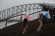 People shelter under umbrellas as they walk up steps to the Opera House, with the Sydney Harbour Bridge seen in the background, on March 2. Thousands of Australians have been ordered to evacuate their homes in Sydney's northwest and elsewhere in New South Wales state as heavy rainfall is flooding rivers and waterways