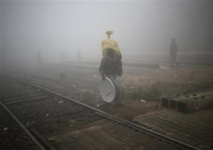 People cross railway tracks on a foggy winter morning in New Delhi