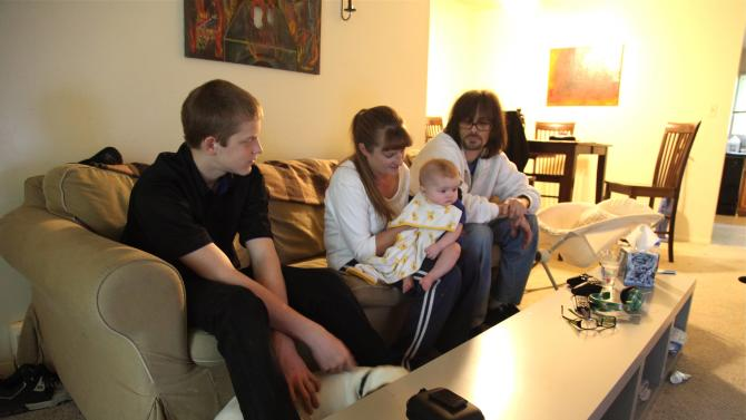 In this Sept. 16, 2011 photo, Kris Fallon holds her 4-month-old daughter Addison, in Palatine, Ill., as her 15-year-old son Gared, left, and husband Jim Fallon look on. The Fallon family has been living in poverty for nearly two years. (AP Photo/Robert Ray)
